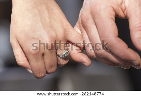 Closeup of couple's hands, woman's hand has engagement ring on - stock photo