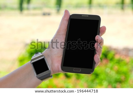 Closeup of couple smartwatch and phablet as the concept of wearable technology - stock photo