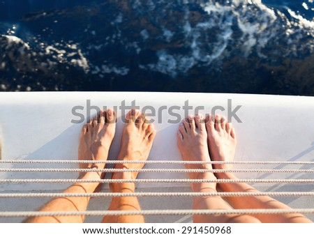Closeup of couples feet on a yacht out a sea. (travel vacation concept)   - stock photo