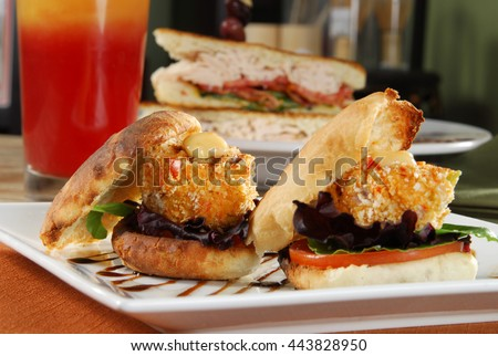 Closeup of crabcake sandwiches with a turkey sandwich in the background - stock photo