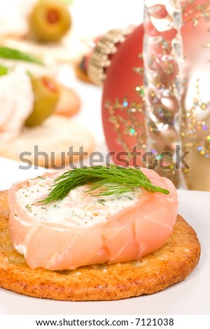 Closeup of cracker with smoked salmon roll with goat cheese and dill on holiday table