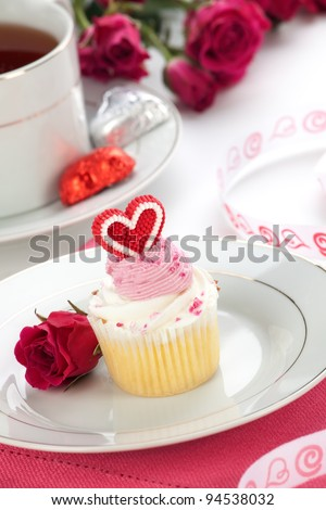 Closeup of cream cupcake on Valentine day with heart shaped decoration. Tea and pink spray roses.