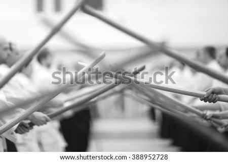 Closeup of crossed bokkens in hands of samurai - stock photo