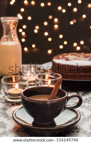 Closeup of Cup of hot coffee on the table with chocolate cake and a bottle of milk with blurry lights. - stock photo