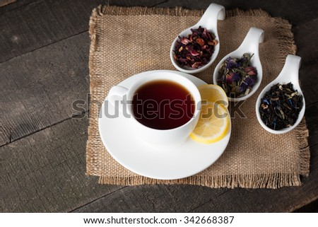 Closeup of cup of tea on vintage wooden background. Black herbal tea with lemon, ginger and honey. hot winter drink