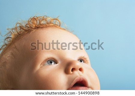 Closeup of cute baby boy looking up isolated on blue background - stock photo