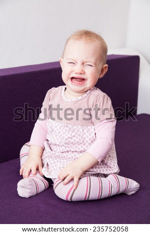 Closeup of cute crying baby girl sitting on the sofa - stock photo