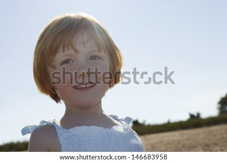 Closeup of cute little girl smiling while looking away at beach - stock photo