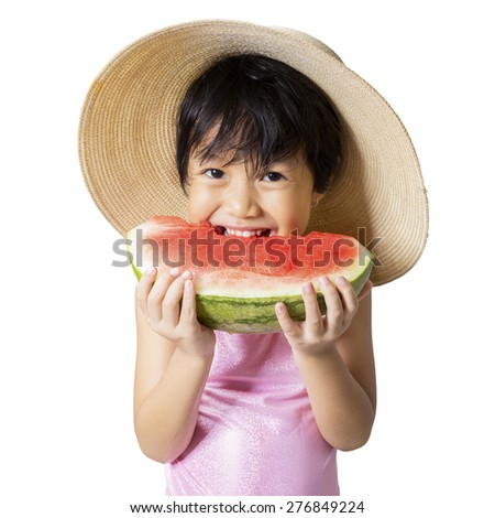 Closeup of cute little girl standing in the studio while eating a fresh watermelon and wearing hat - stock photo