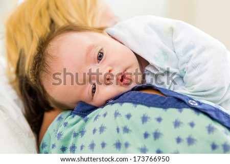 Closeup of cute newborn babygirl resting on mother's shoulder in hospital - stock photo