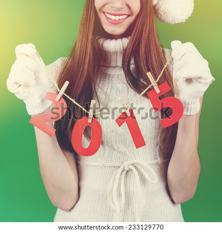Closeup of cute young Christmas woman's hands holding 2015 number against green background. Square format image. - stock photo