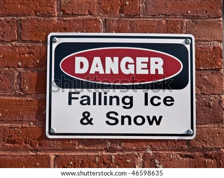 Closeup of Danger Falling ice and snow sign mounted on old brick building wall.