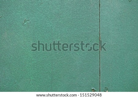 Closeup of dark green wall with screw holes and nails