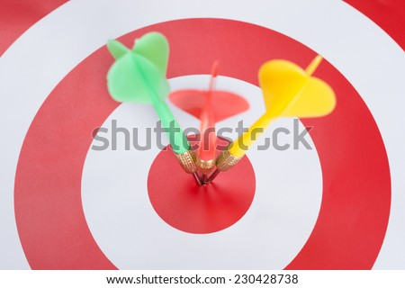 Closeup of darts on concentric red and white target - stock photo