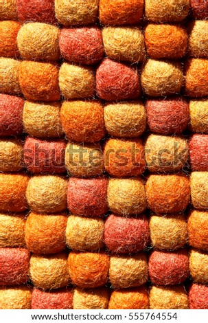 Closeup of decorative abstract carpet texture with colorful bright beads of synthetic fibers. Yellow, orange and red tones.Useful for background.