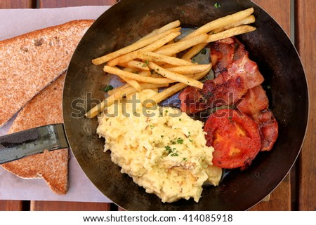 Closeup of delicious breakfast - bacon,scrambled eggs, grilled tomato and fries in a pan, with toast on the side - stock photo