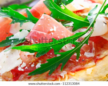 Closeup of delicious fresh ingredients used as a topping for Italian pizza with thinly sliced ham, tomato, fresh herbs,rucola and cheese - stock photo