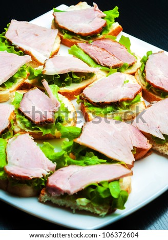 Closeup of delicious ham and salad canapes sandwiches lying on a white plate. - stock photo