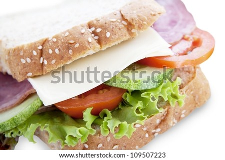 Closeup of delicious sandwich with lettuce, cheese, cucumber, meat, and tomato