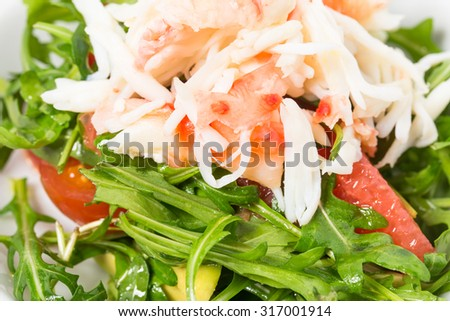 Closeup of delicious snow crab salad with pomelo and arugula topped with pine nuts. Macro. Photo can be used as a whole background.
