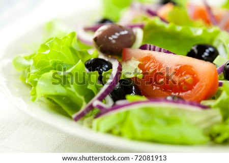 Closeup of delicious vegetable salad with olives - stock photo