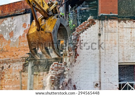 Closeup of Demolition by Backhoe of Old Building - stock photo