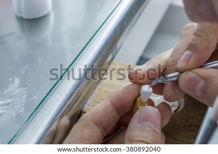 Closeup of dental technician applying ceramics to teeth before put into furnace - stock photo
