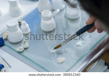 Closeup of dental technician putting the ceramic material in powder on the glass and mixing the composition. - stock photo