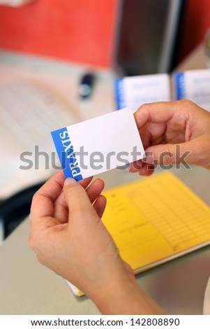 Closeup of dentist's hands holding blank note at counter