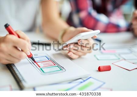 Closeup of designers creating mobile app prototype - stock photo