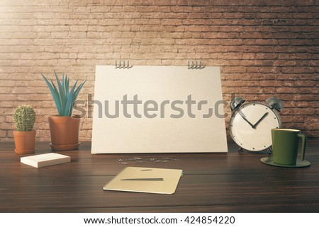 Closeup of desktop with blank card, plants, coffee cup, alarm clock and stationery items on red brick background. Mock up, 3D Rendering - stock photo