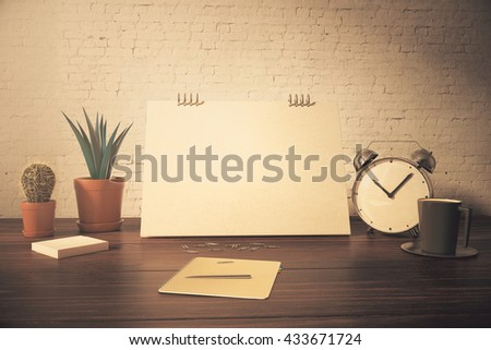 Closeup of desktop with blank card, plants, coffee cup, alarm clock and stationery items on white brick background. Toned image. Mock up, 3D Rendering - stock photo