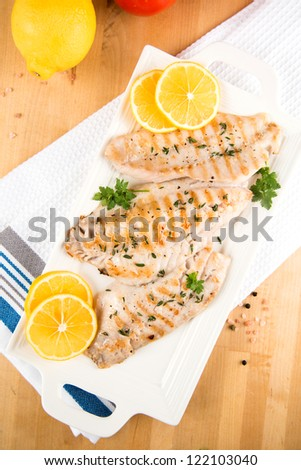 Closeup of Dinner Plate with Grilled White Fish and Lemons - stock photo