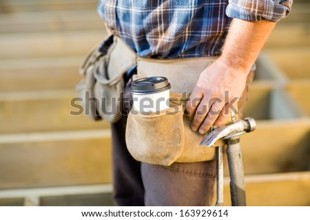 Closeup of disposable coffee cup and hammer on carpenter's tool belt outdoors - stock photo