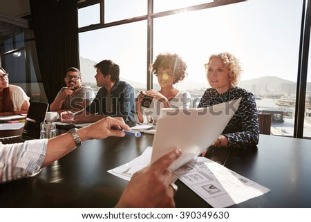 Closeup of documents in hands of young man explaining project plan to coworkers during a meeting in office. - stock photo