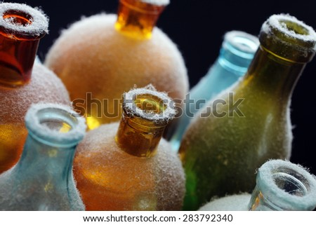 Closeup of domestic dust on vintage glass bottles used as decoration. Narrow DOF. - stock photo