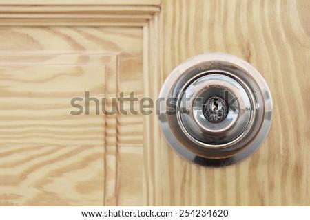 closeup of doorknob with wooden door - stock photo