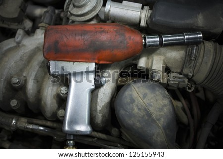 Closeup of drill under hood of car