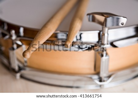 Closeup of drumsticks over a snare drum and tuner - stock photo