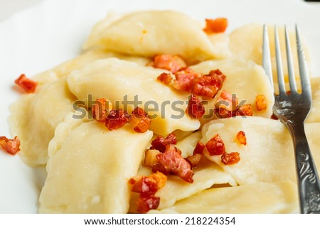 Closeup of dumplings sprinkled with pork scratchings with fork as food background. Traditional polish (Poland) cuisine. - stock photo