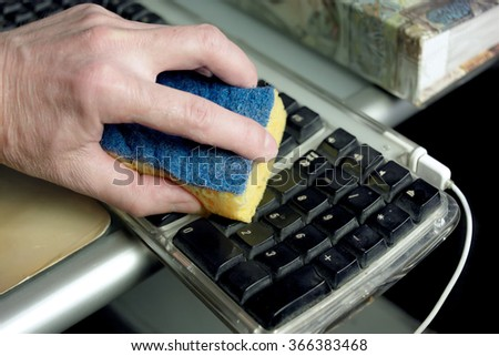Closeup of dusty computer keyboard and hand wiping it with sponge, closeup indoor shot - stock photo
