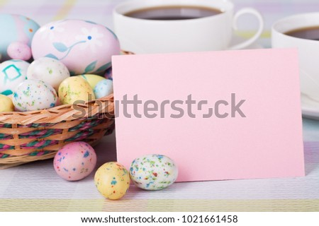 Closeup of Easter candy and blank envelope with basket and coffee in background