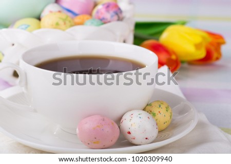 Closeup of Easter candy and cup of coffee with tulips and basket of eggs and candy in background