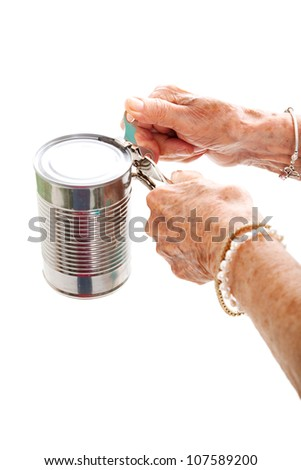 Closeup of elderly hands, with arthritis, struggling to use a can opener.  Isolated on white. - stock photo