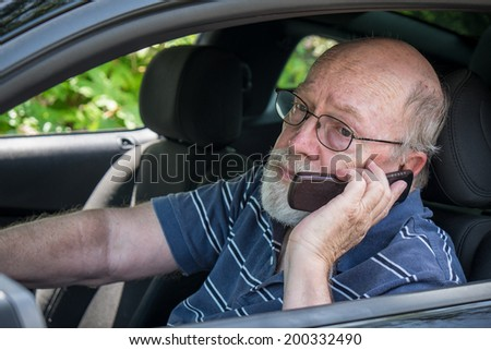 Closeup of elderly man in car on cell phone
