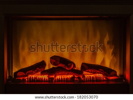 Closeup of electric artificial fireplace with orange fire flame interior - stock photo