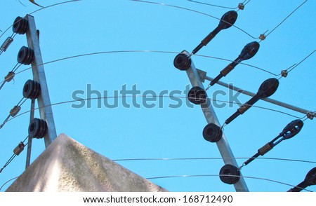 Closeup of electric fence installation on boundary wall against blue sky - stock photo