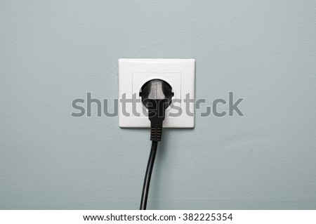 Closeup of electric socket with black cable plugged in as energy source concept - stock photo