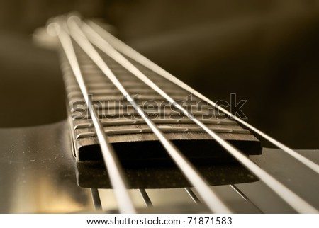 closeup of electrical bass guitar fingerboard, sepia - stock photo