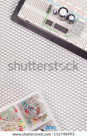 Closeup of electrical circuit on breadboard on isolated vented steel background with copy space